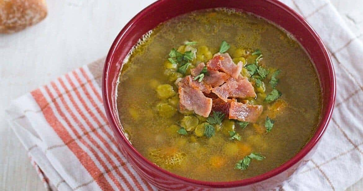 split pea soup in a red bowl with bacon on top