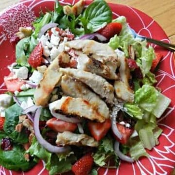 Chicken and strawberry salad on a red plate