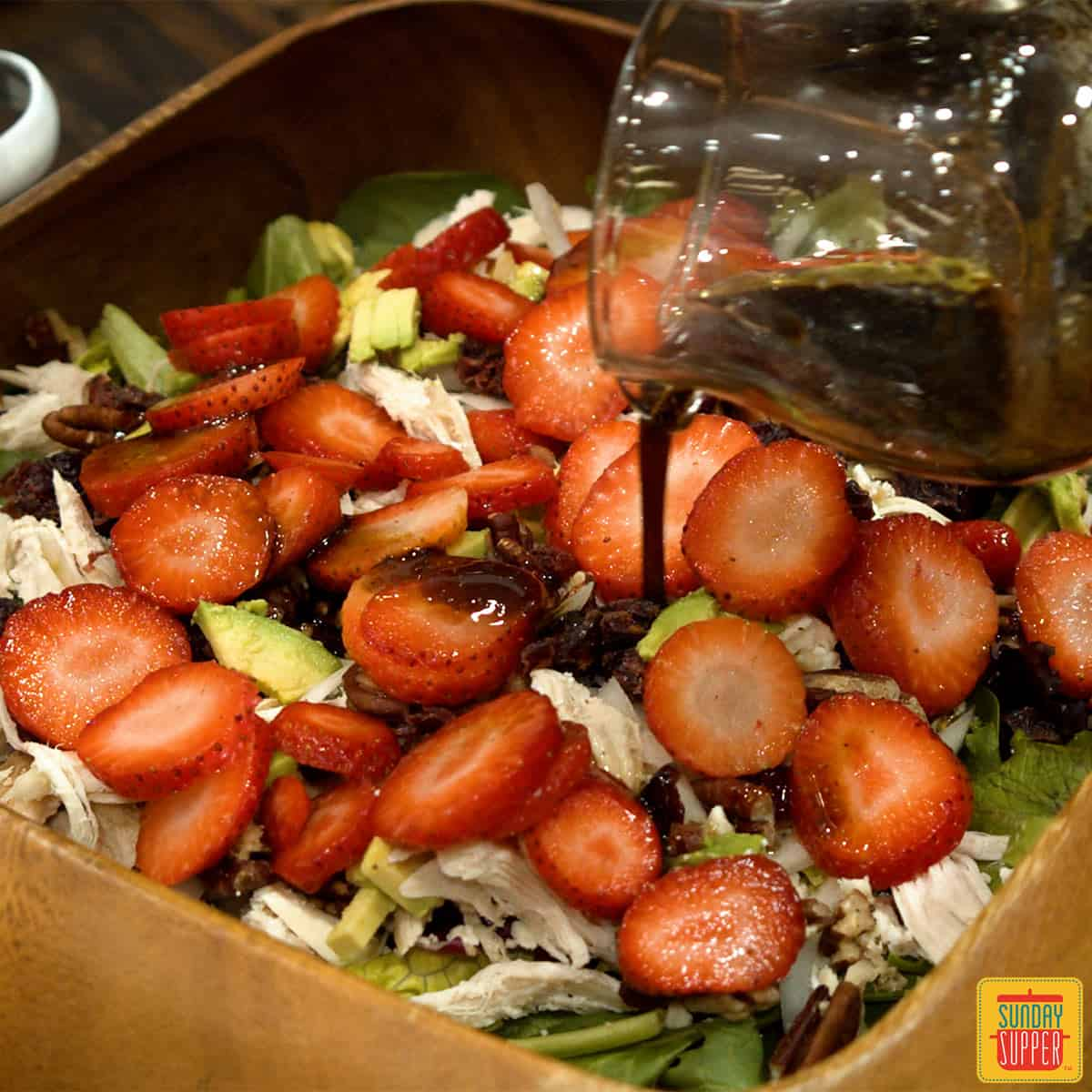 Pouring dressing over chicken salad recipe with strawberries