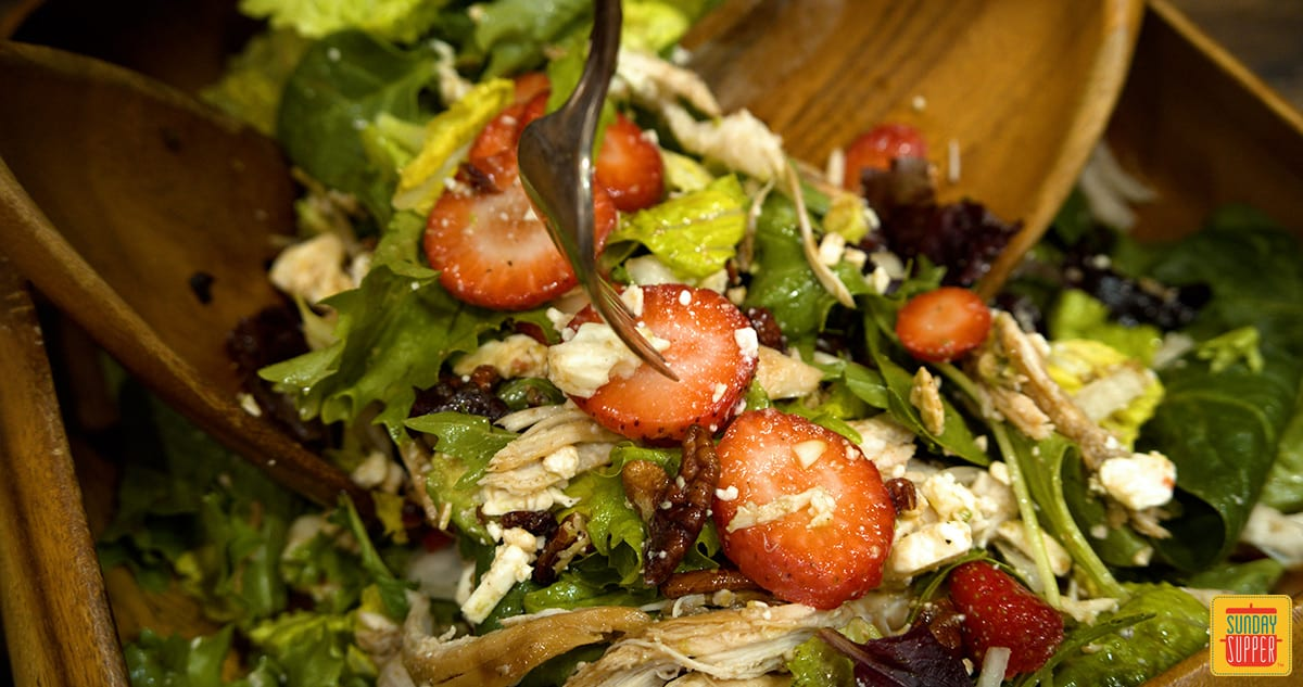 Mixing strawberry chicken salad in a bowl up close