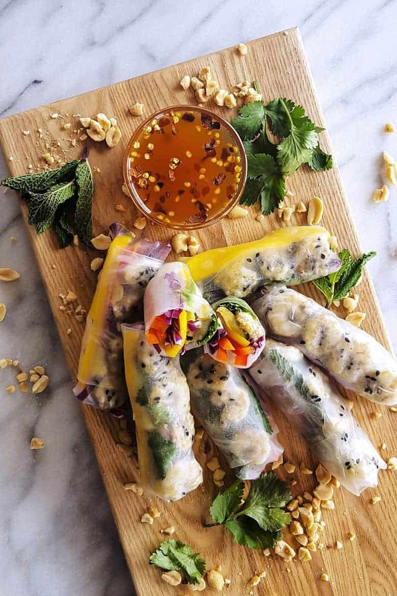 Sesame lime roasted shrimp summer rolls with mango and avocado on a cutting board from Feast in Thyme
