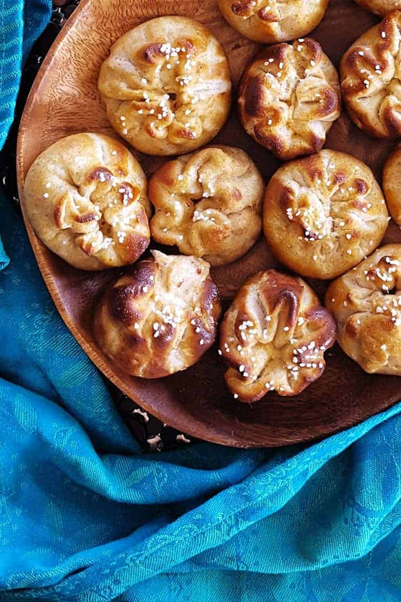 Crab Rangoon Pretzel Buns on a wooden plate from Feast in Thyme