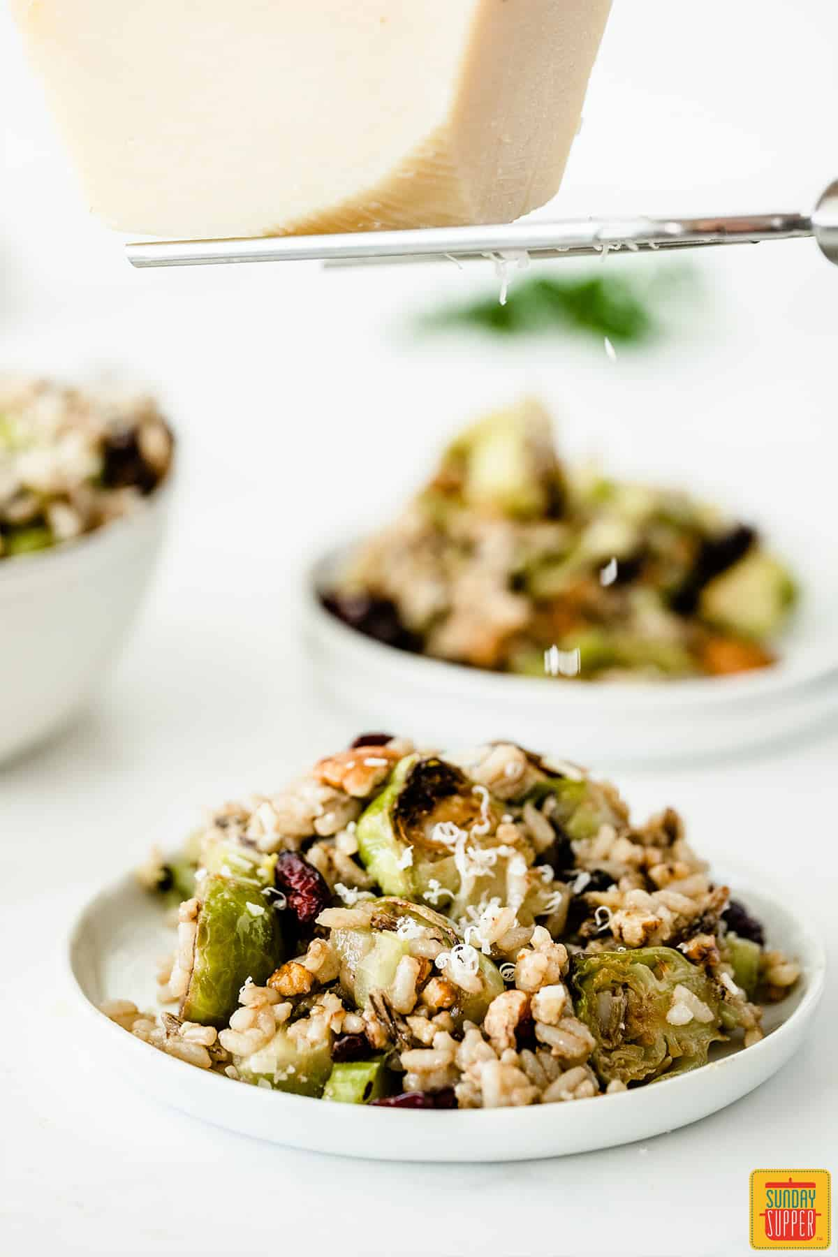 Shaving cheese over roasted brussels sprouts wild rice salad