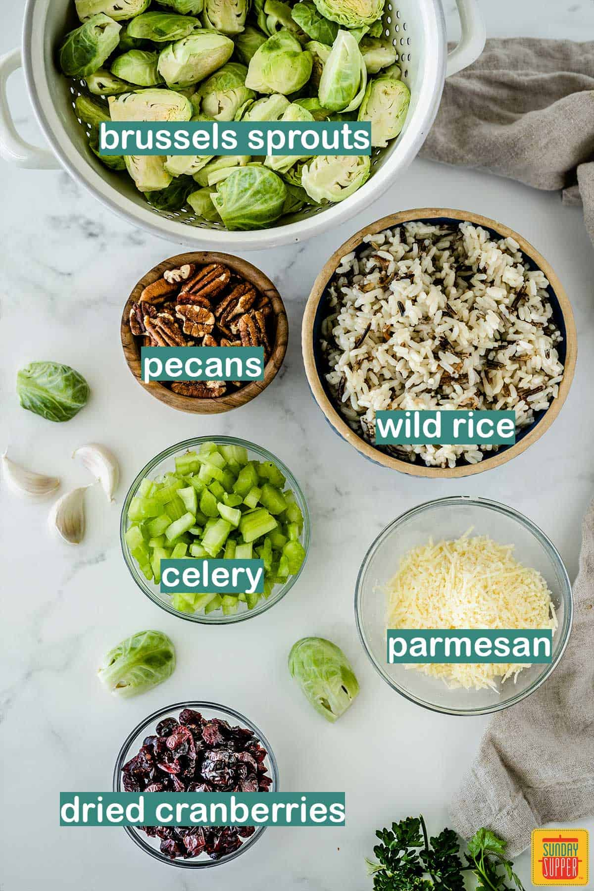 Ingredients to make Roasted brussels sprouts salad on a white surface with labels