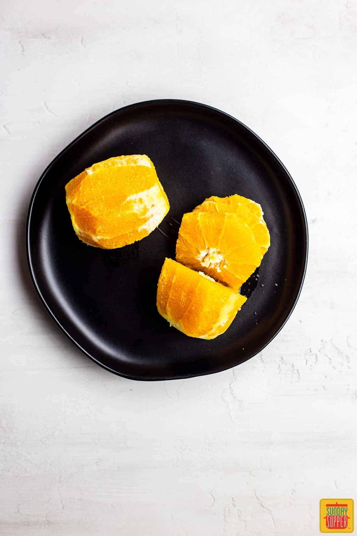 Fresh cut oranges on a black plate