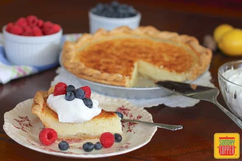 A slice of southern buttermilk pie topped with whipped cream and berries in front of the whole pie with a cake slicer