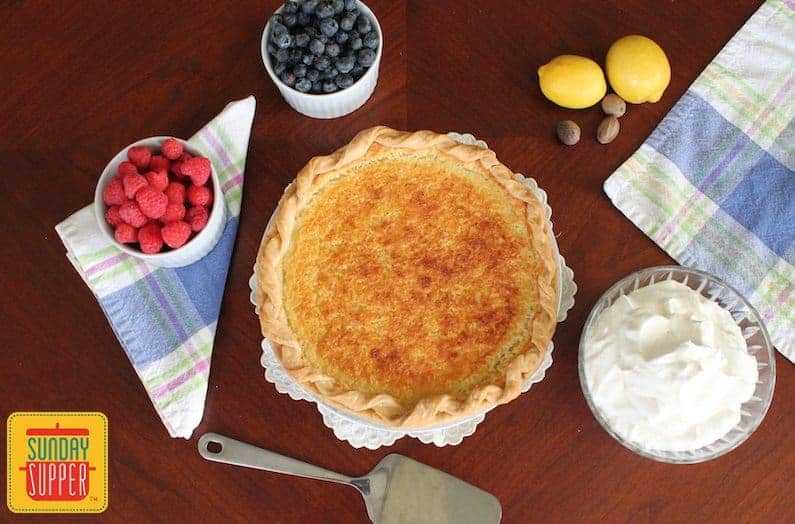 Whole southern buttermilk pie next to whipped cream and fresh berries in bowls with two lemons and nutmegs on the table nearby