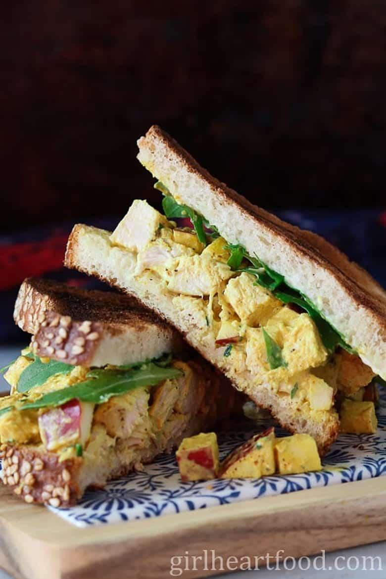 Curry chicken salad sandwiches on a cutting board by Girl Heart Food