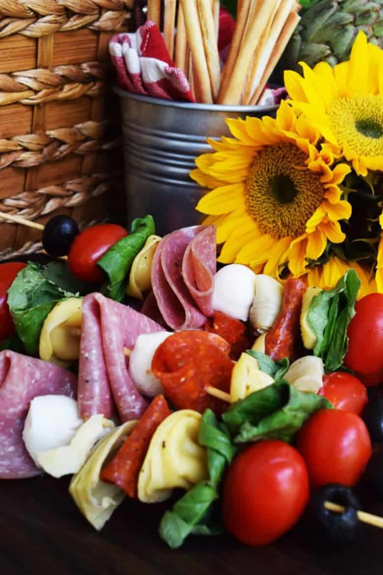 Antipasto skewers in front of sunflowers by Soulfully Made