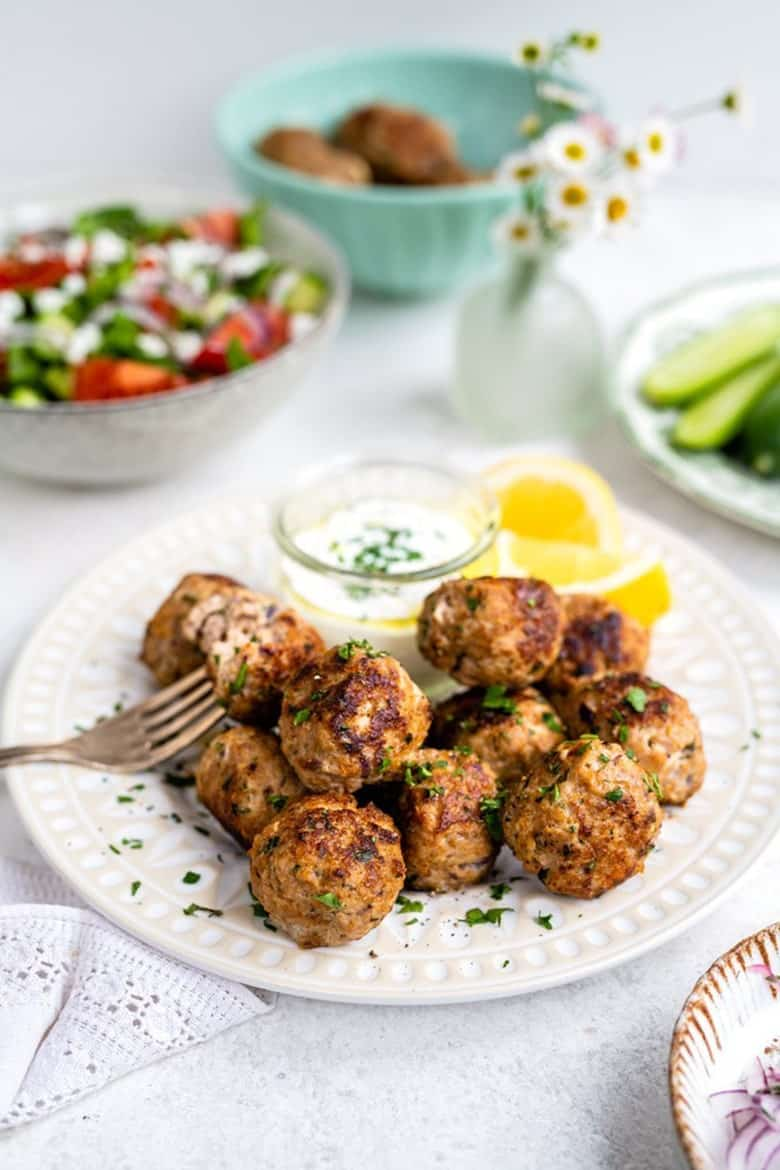 Greek meatballs by Supergolden Bakes served on a plate stacked with tzatziki sauce to the side