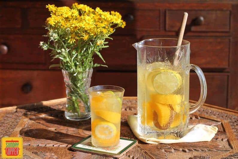 citrus peach sangria in a pitcher with a wooden stirring spoon and a glass of sangria to the side by some flowers
