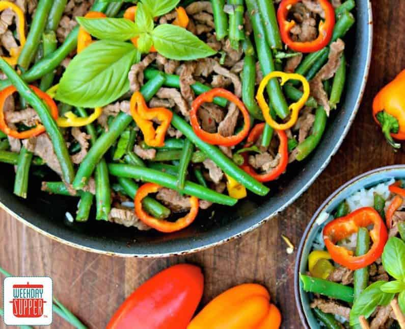 Asian Beef and Green Bean Stir-fry in a skillet with a bowl of stir fry to the side