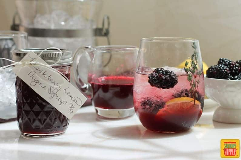 Blackberry Lemon Thyme Syrup in a jar and glass next to a glass of a drink using the syrup and fresh blackberries