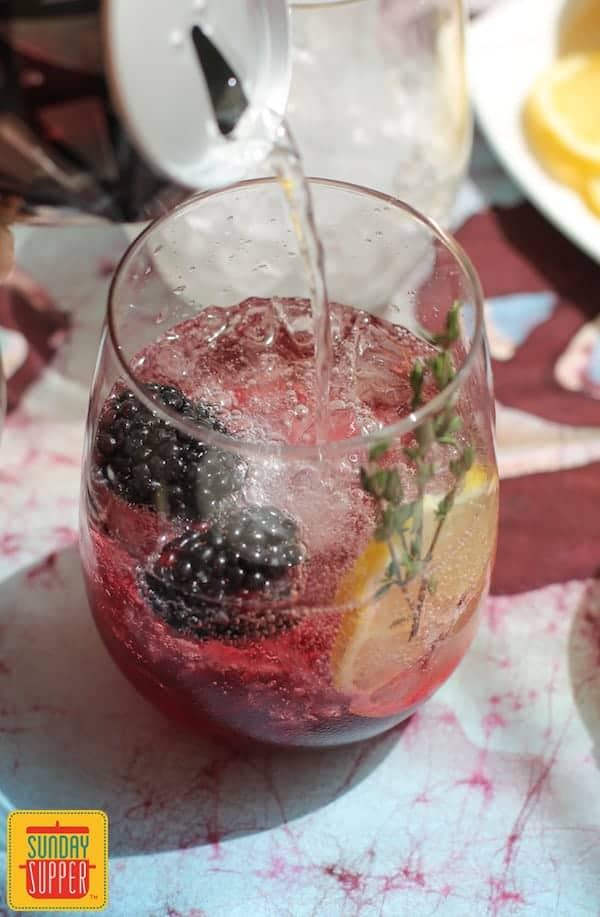Pouring a drink with blackberry thyme syrup into a glass with a lemon slice and blackberries