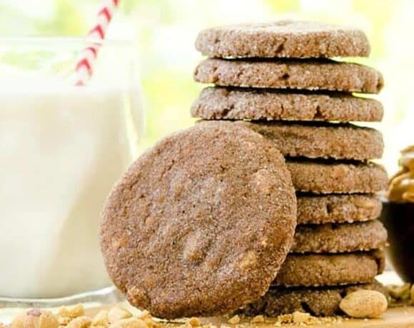 Mexican chocolate cookies stacked up next to a glass of milk