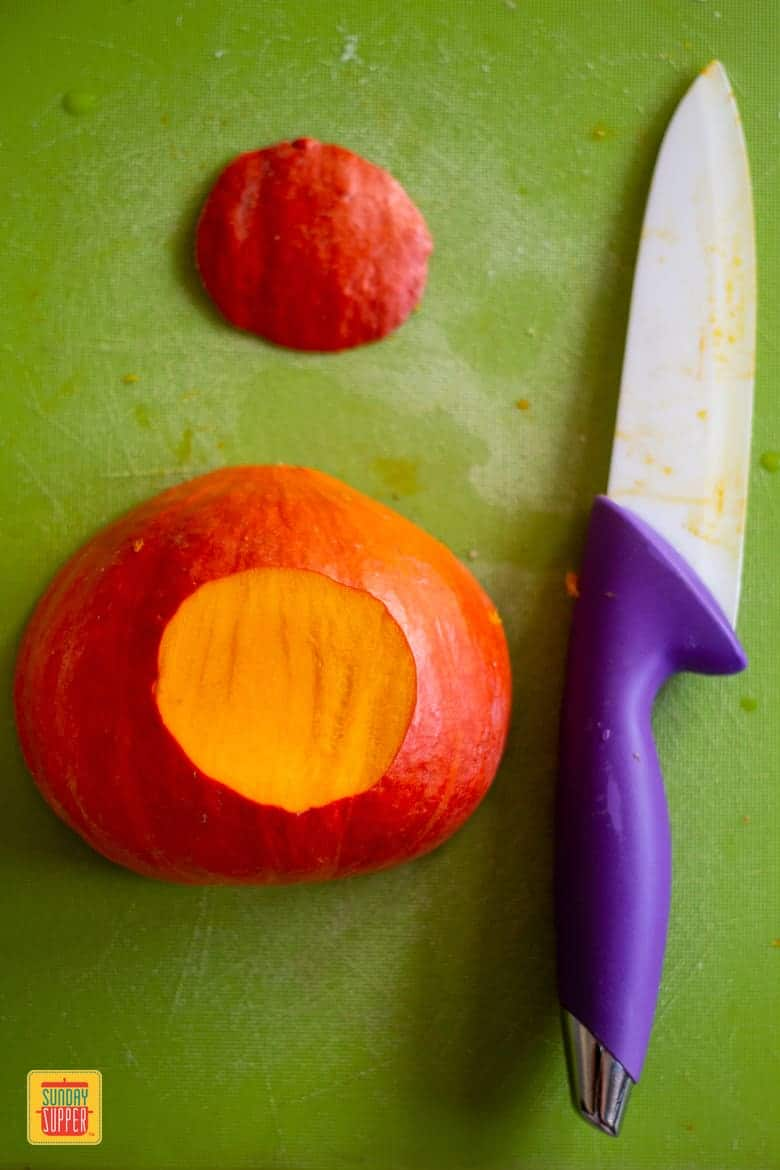Kuri squash half with a sliver cut off the bottom next to a knife