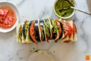 An eggplant sliced and stuffed with tomato, cheese, and pesto