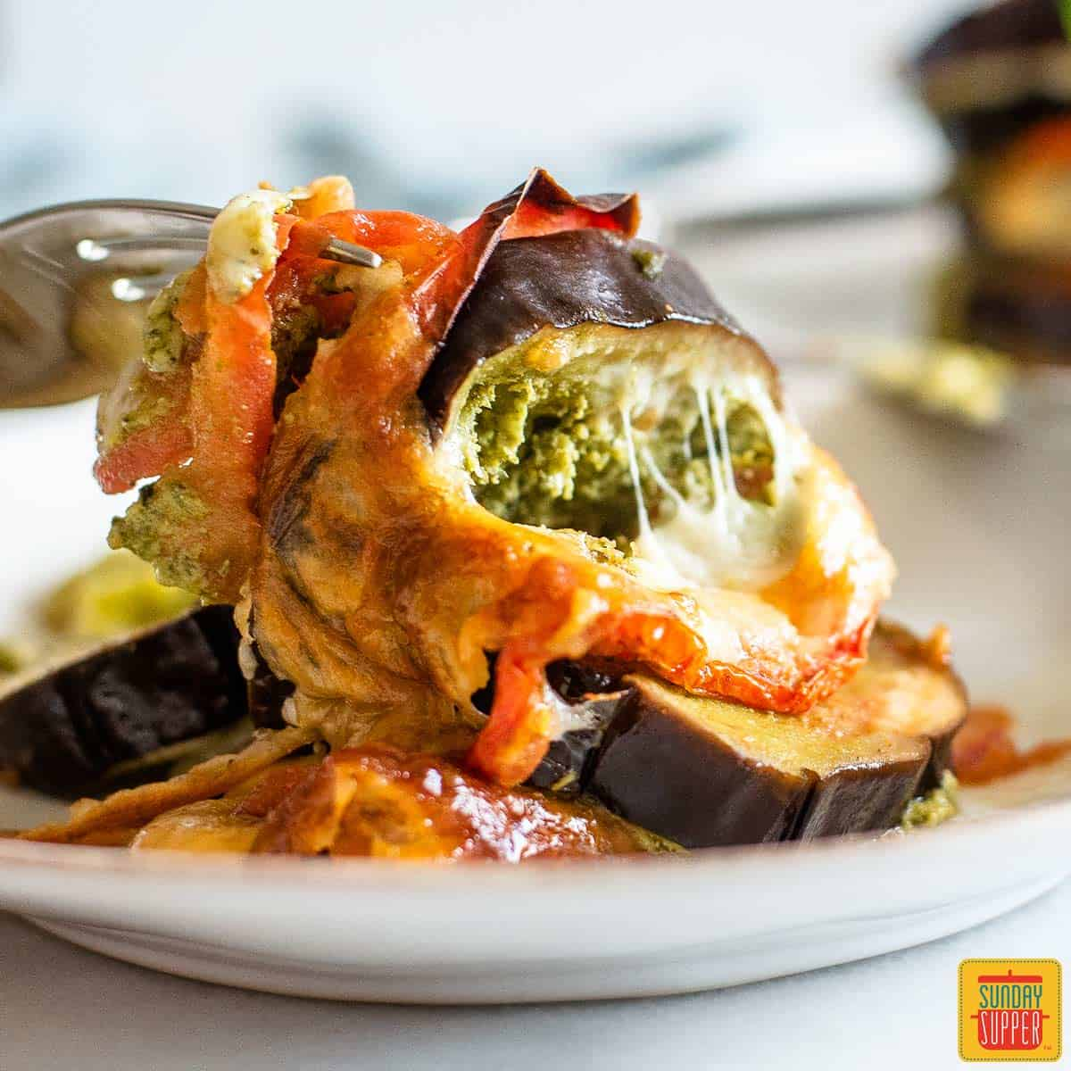 Digging into slices of caprese roasted eggplant recipe with a fork on a white plate