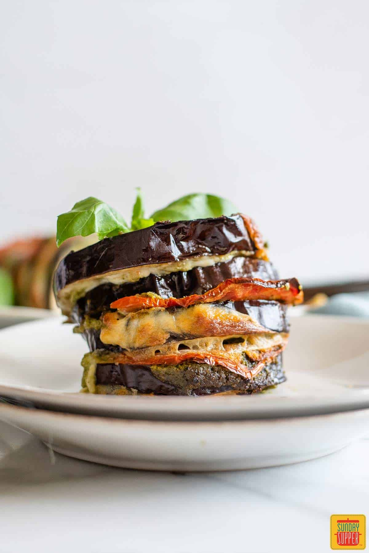 Slices of roasted eggplant stacked on top of each other stuffed with caprese and topped with basil