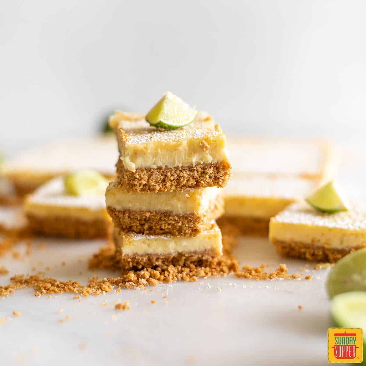 A stack of three key lime pie bars next to the remaining pie squares