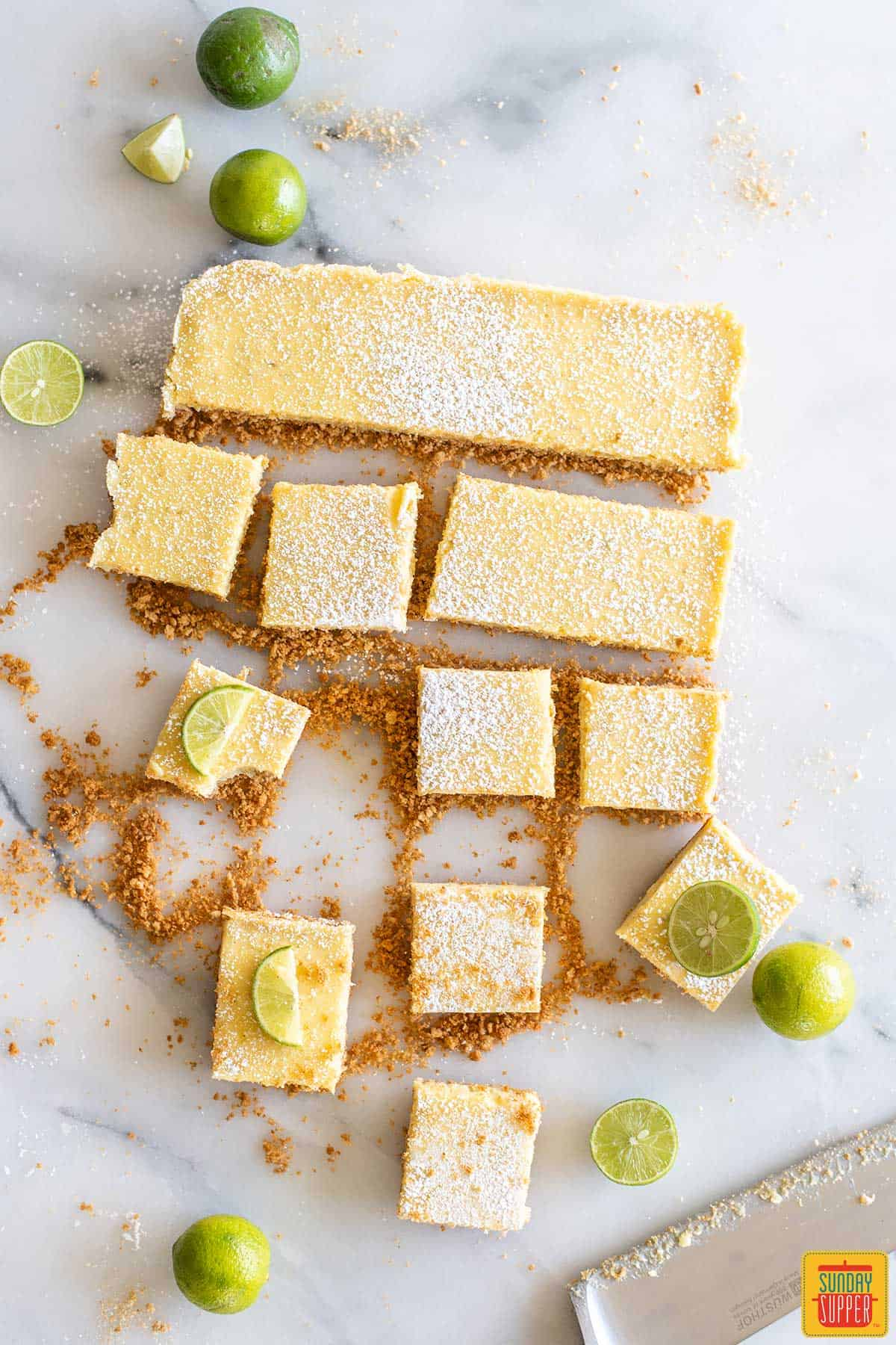 Key lime bars cut into slices next to the remaining uncut pieces of key lime pie