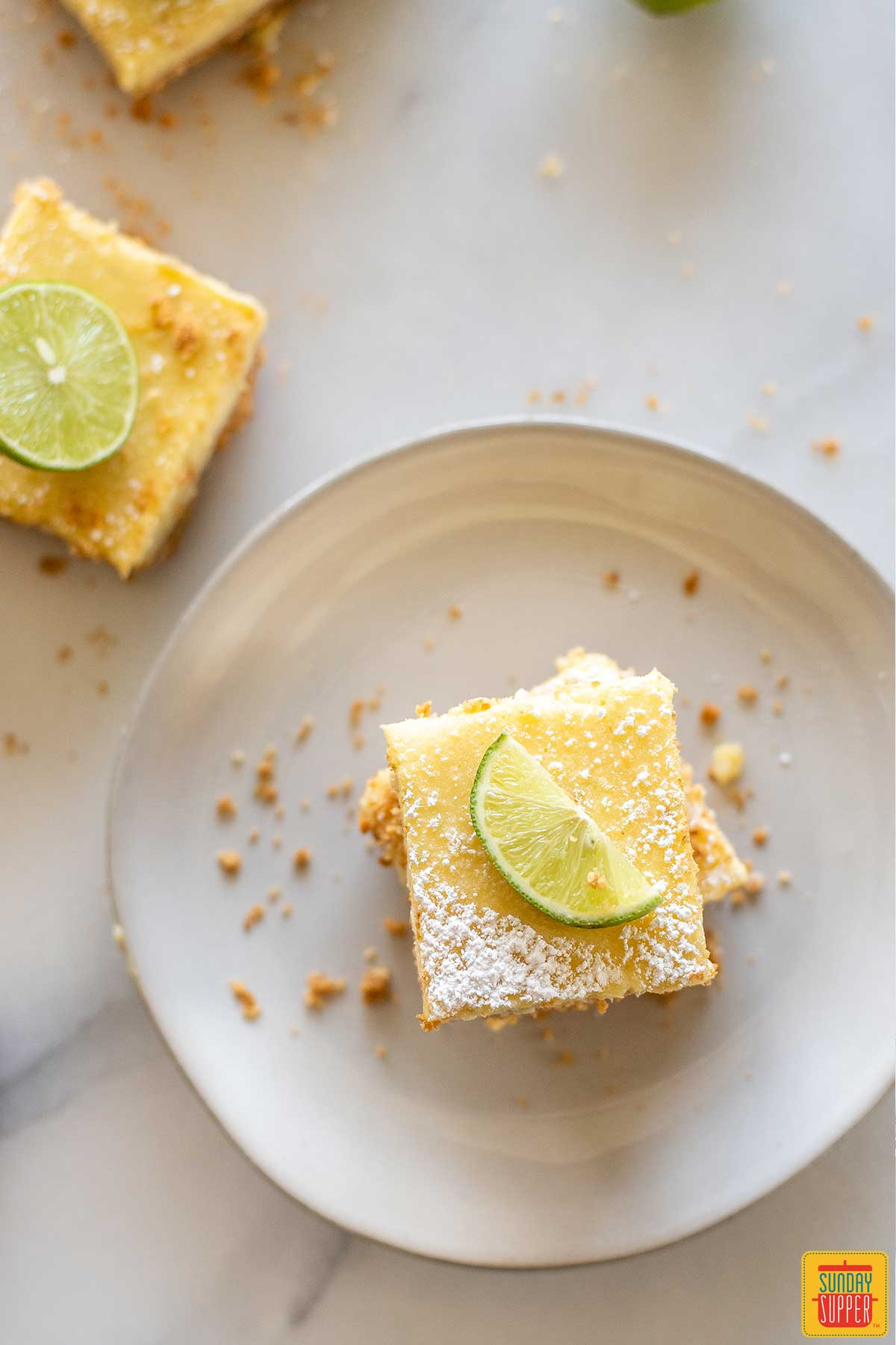 Two key lime bars on a plate next to a third beside the plate