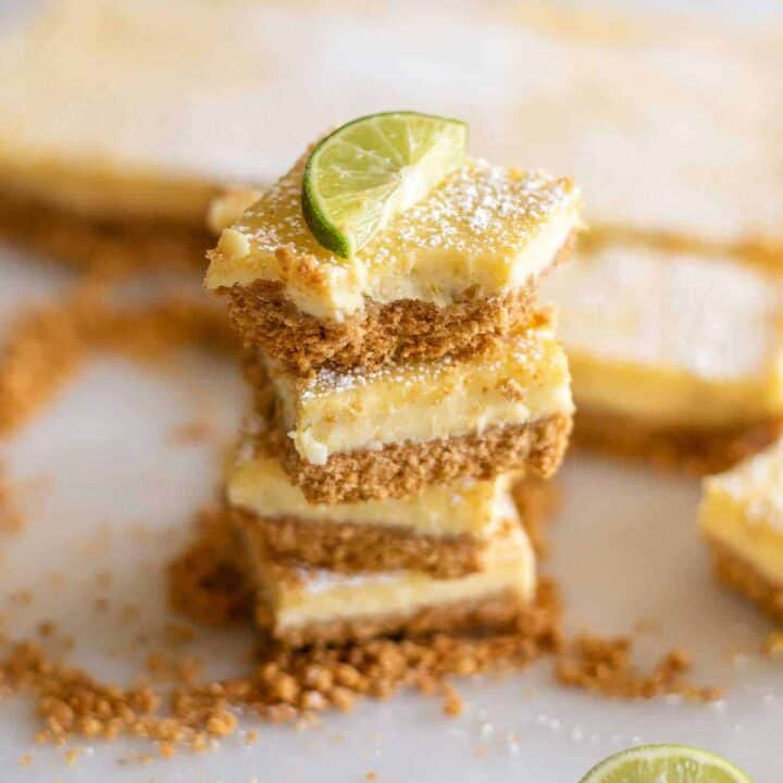 Three key lime pie bars stacked on top of each other surrounded by cookie crumbles with a lime slice on top