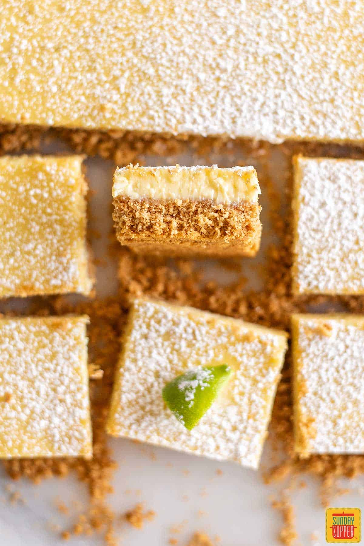 Top-down view of key lime pie squares; one is turned so you can see the crust-to-filling ratio