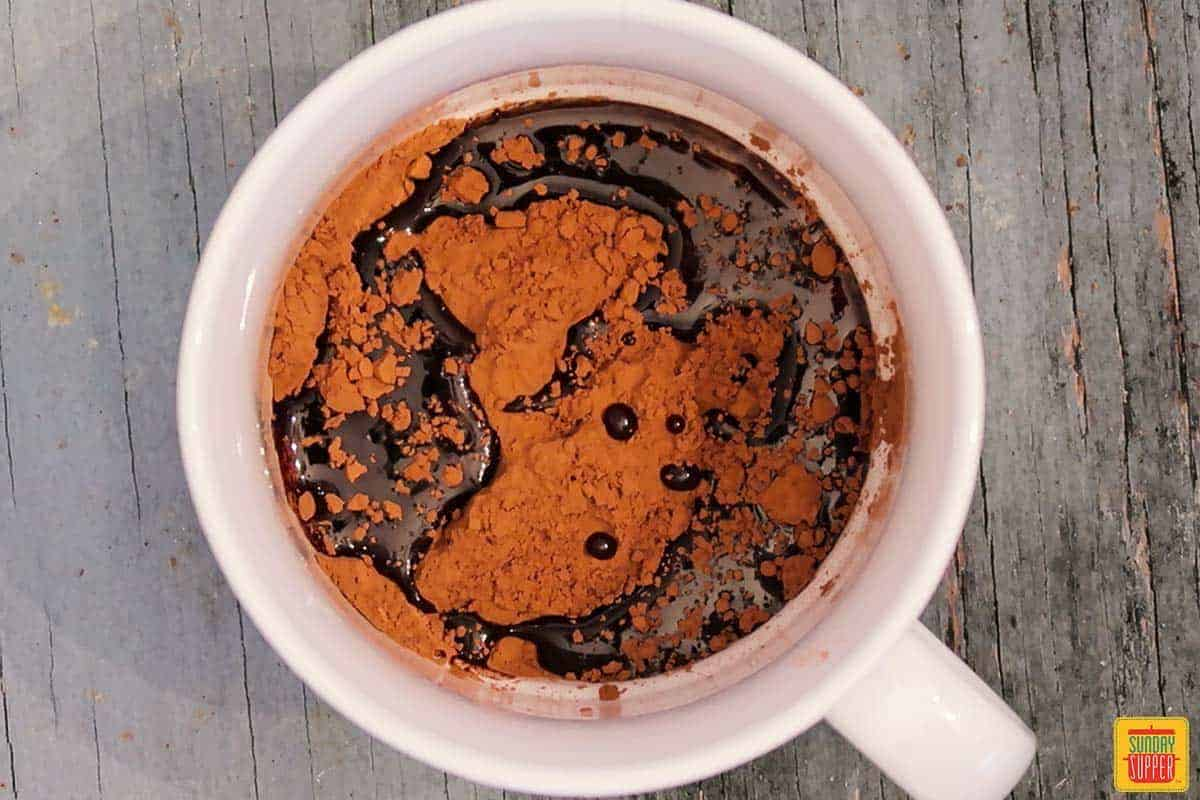 Mixing cocoa powder with oil for brownie in a mug