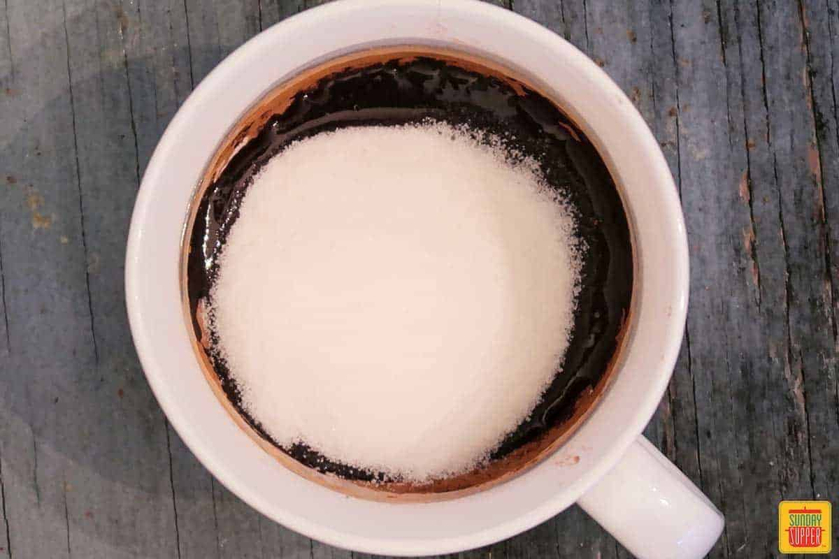 Adding sugar to the brownie in a mug