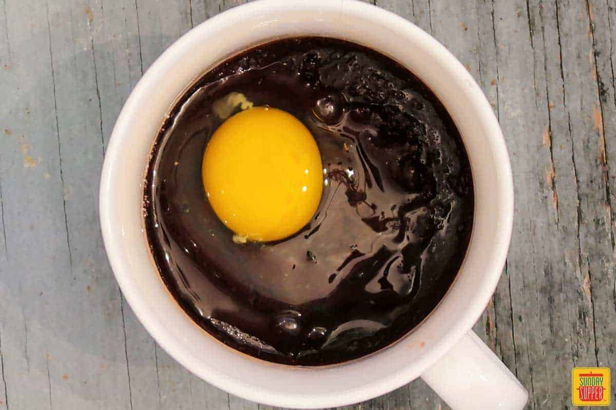 Adding egg to brownie in a mug