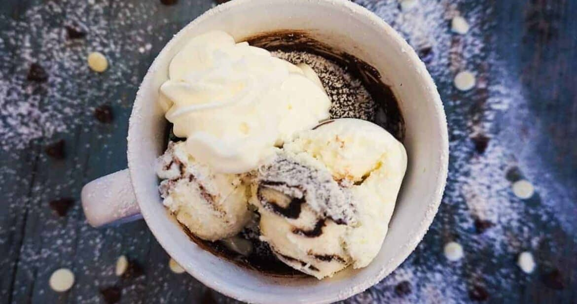 Brownie in a mug with whipped cream and ice cream on a table with chocolate chips spread around