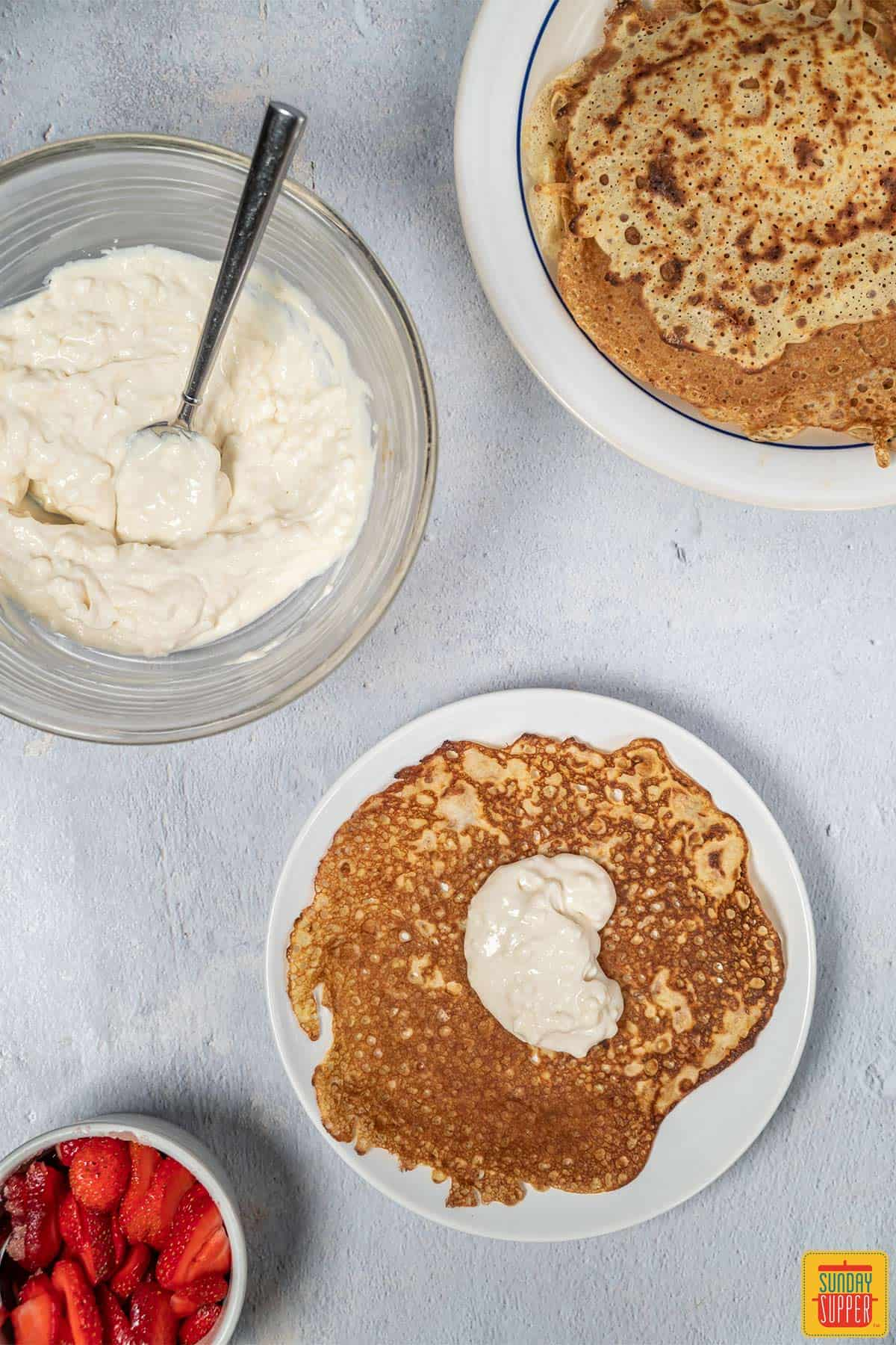 Adding cream to crepes on a plate
