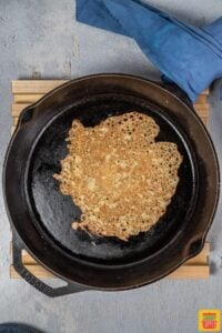 Crepes cooking in a black skillet