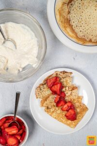 Strawberry crepes on a plate with fresh berries