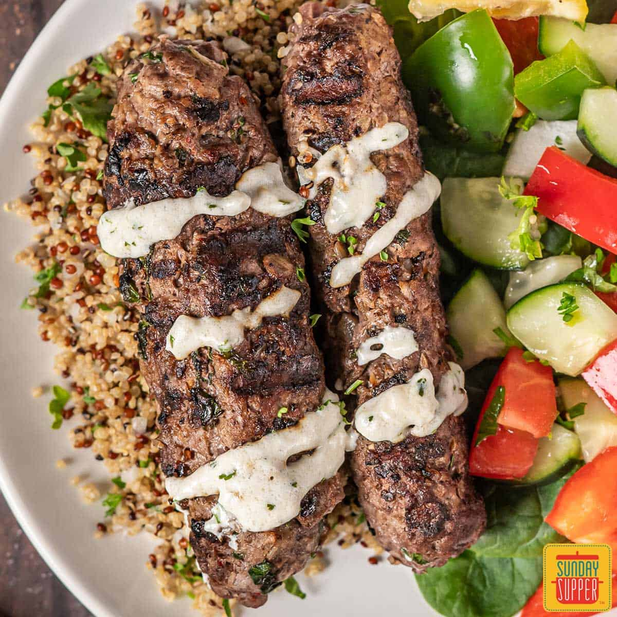 Beef kofta on a plate with cream sauce, couscous and a cucumber salad