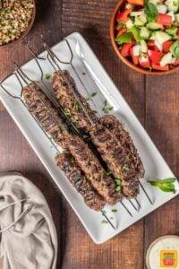 Grilled Lebanese kebabs on a white platter