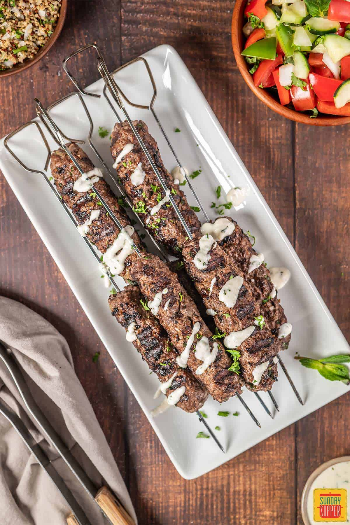 Beef kofta kebabs on a white plate with sauce on top