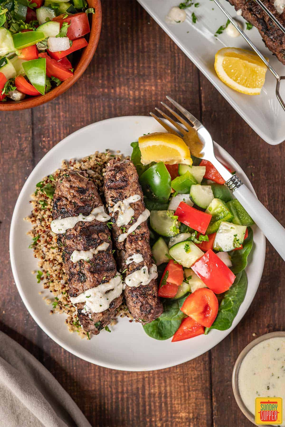 Lebanese beef kofta on a plate with couscous and cucumber salad