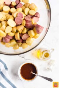 Bowl of sauce mix with a spoon in it next to fingerling potatoes in a glass bowl