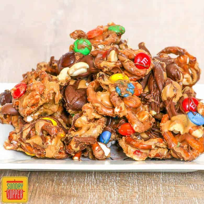 Pretzels covered in chocolate and peanut butter with M&Ms and peanuts on a white plate
