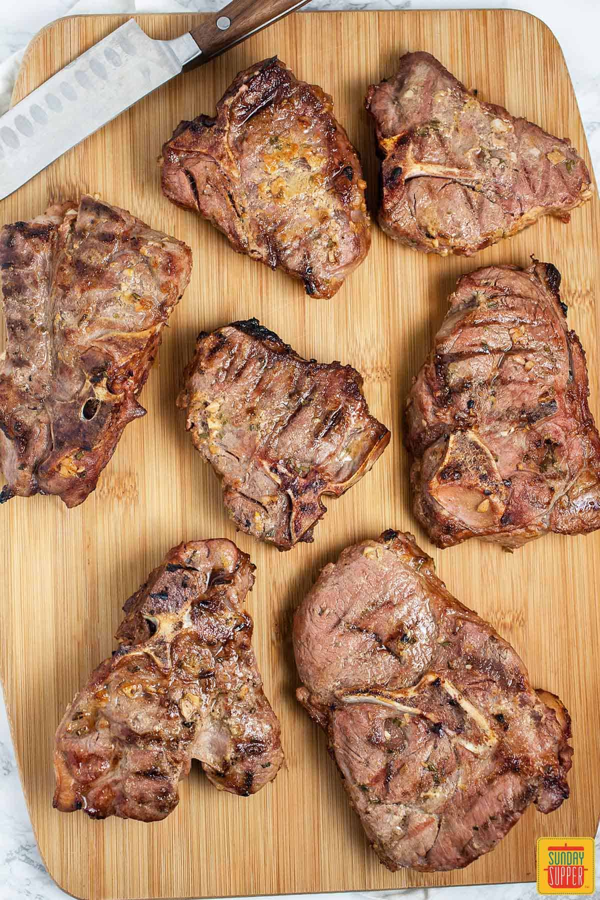 A cutting board of grilled lamb chops ready to serve
