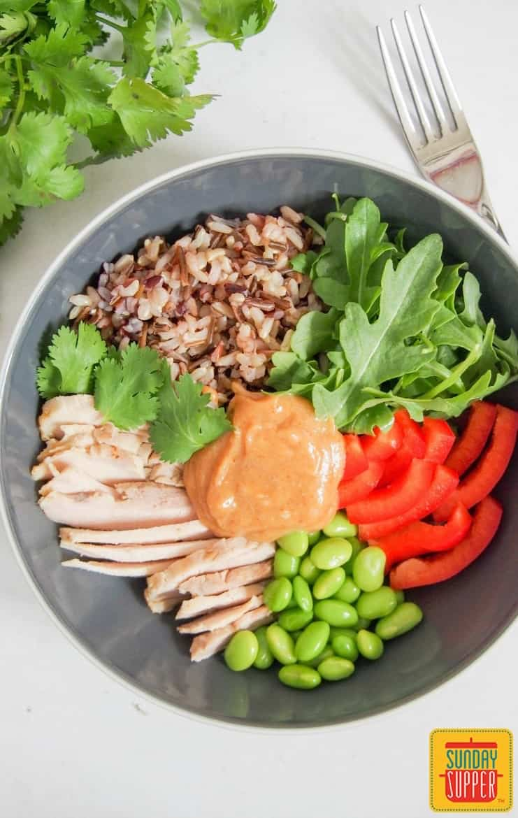 Thai style chicken buddha bowl in a black bowl with sauce on top and a fork to the side