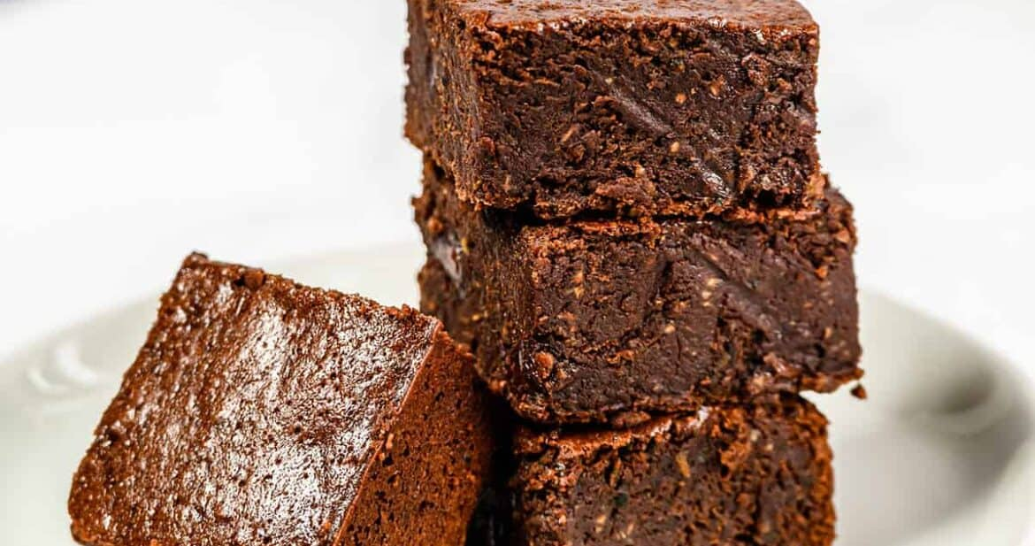 Four zucchini brownies with coconut oil on a plate
