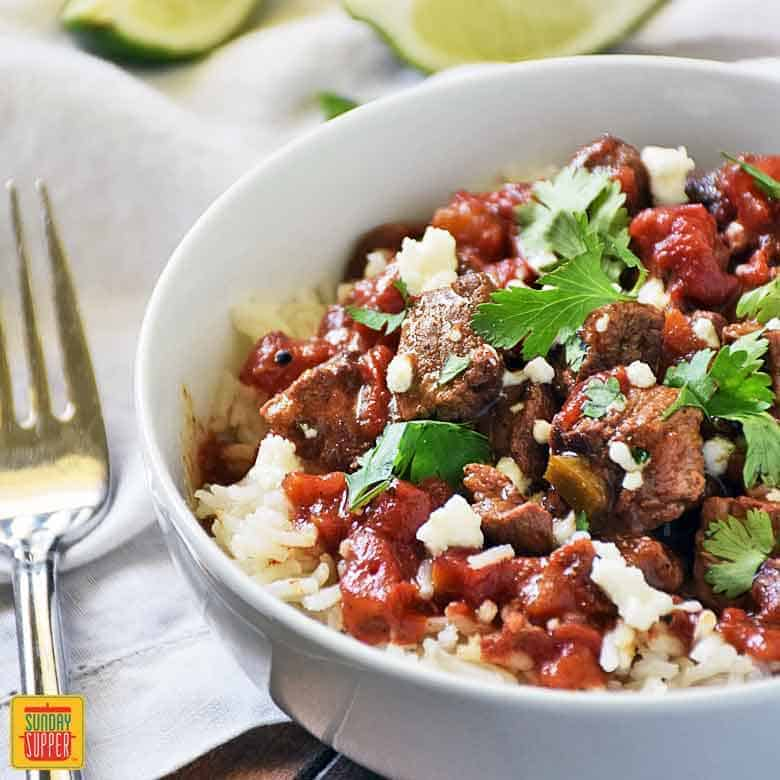 Carne PIcada served over rice in a bowl and garnished with cilantro