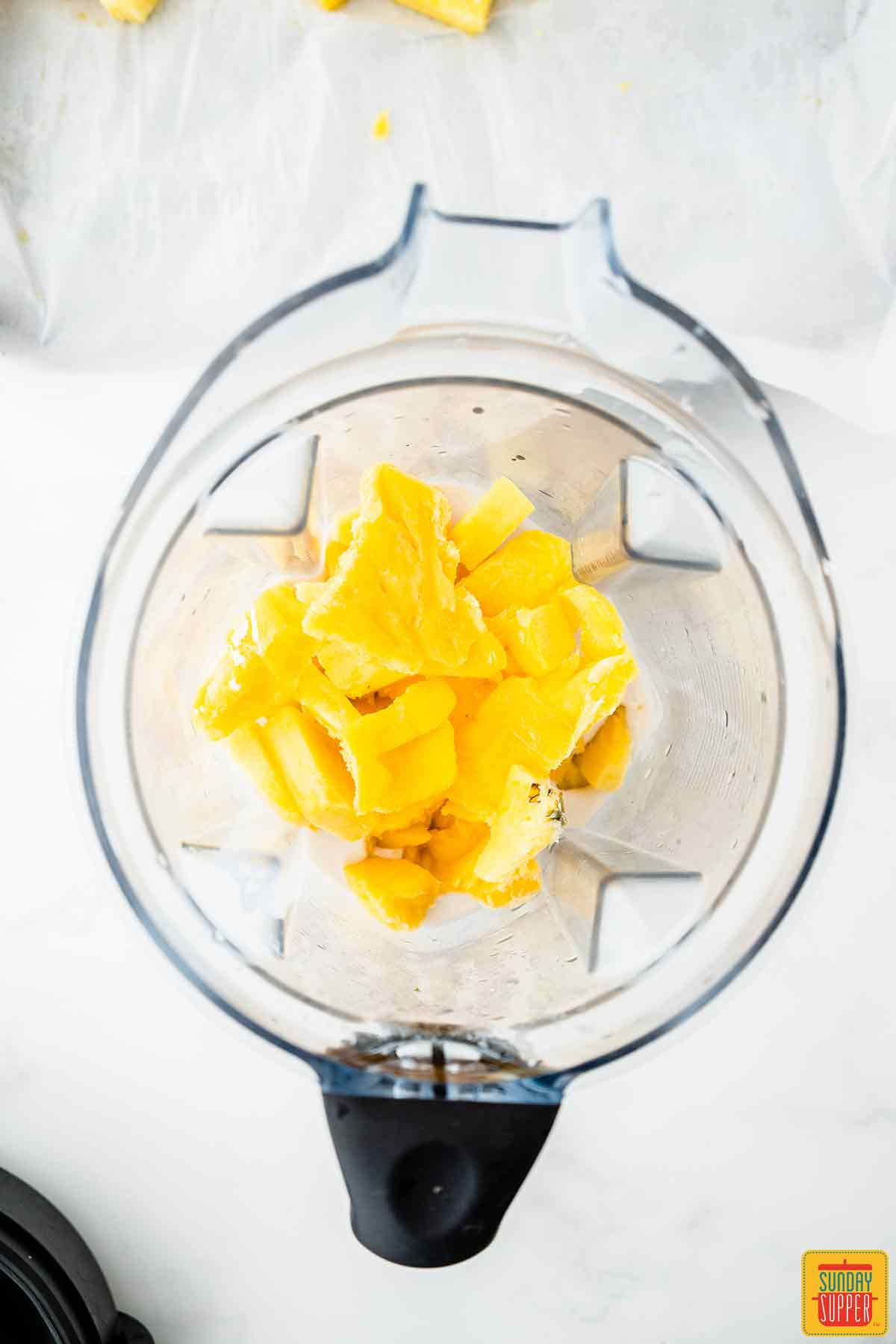 Adding mango to a blender with rum and coconut milk to make coconut rum cocktail