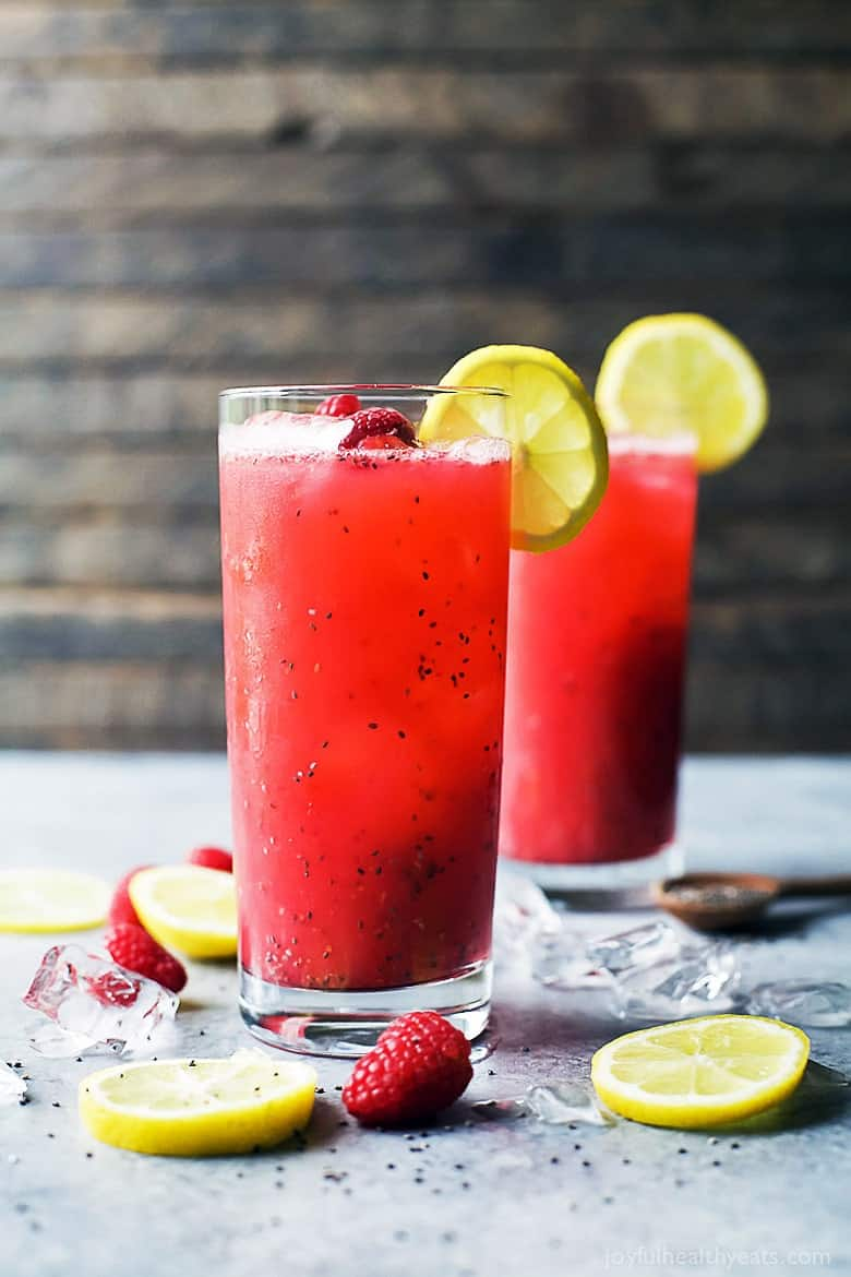 Simple Mixed Drinks - Chia Raspeberry Lemonade Spritzer in two glasses with lemon slices and raspberries on the table