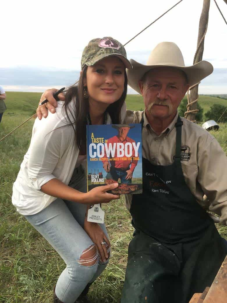 Cowboy Kent Rollins with his book and a fan outdoors