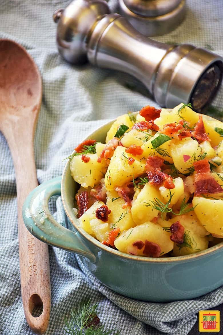 German potato salad served with bacon bits, fresh dill, and parsley in a blue bowl with handles