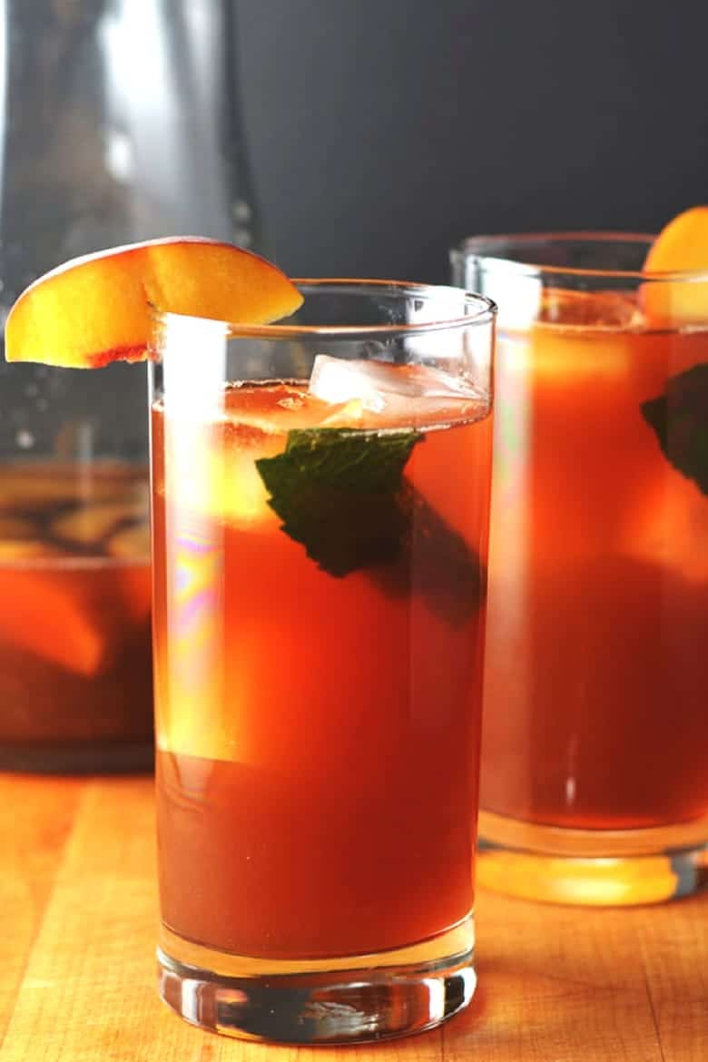 Simple Mixed Drinks - Two glasses of Bourbon Peach Sweet Tea with peach slices on the rim of the glass